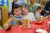 Students Making Gingerbread Houses Together